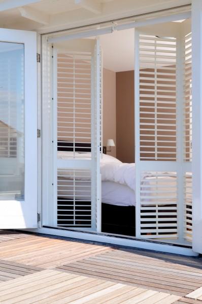 白い木製の折れ戸鎧戸で庭とつながるベッドルーム1