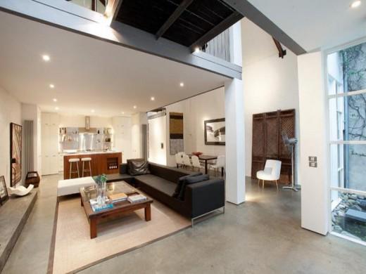 大きく開口する格子入りガラスドアで屋内とフラットにつながる石畳敷きのテラスから屋内のリビングを 吹き抜け