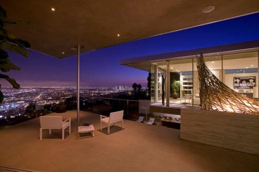 高台に建つ家の開放的な全開口スライドドアのベッドルームに隣接するベランダからの夜景