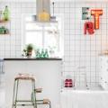 壁全面が白いタイル貼りの白基調のキッチン 壁にはタイポグラフィ サインランプ