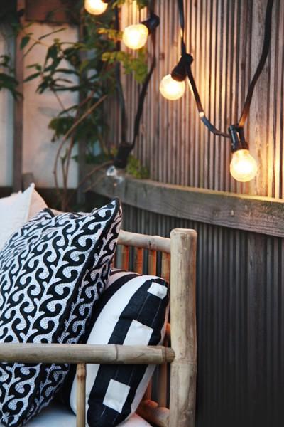 裸電球でライトアップされるバンブーのソファのあるテラス、少し和風