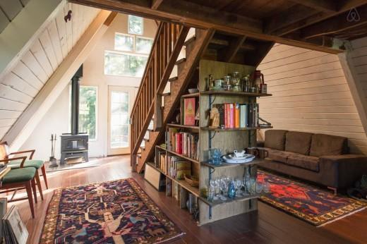 森の中に建つコンパクトなAフレームの山小屋 奥から玄関側 階段下の収納を