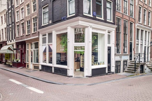 半屋外の開放的なテラス的スペースにドリンク用の冷蔵庫の置かれたアムステルダムのフレッシュジュース・カフェテリアの外観