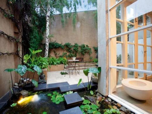 大きく開口する格子入りガラスドアで屋内とフラットにつながる石畳敷きのテラスのサイドの池.