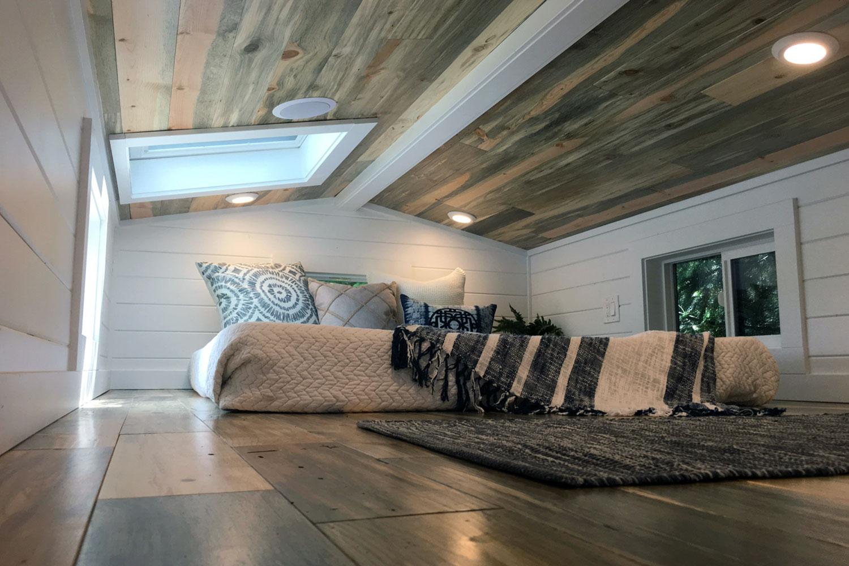 ロフトの天窓付きの低い勾配天井の下のベッドルーム