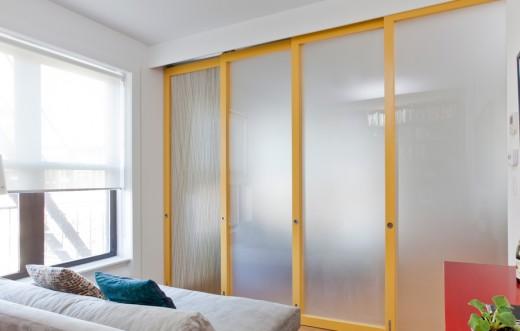 木製フレームとアクリル樹脂の半透明パネルのスライドドアで仕切られるリビングの一画 小部屋側から ドアを閉めたところ