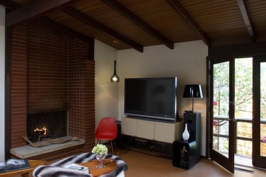 ミッドセンチュリーハウスの暖炉のある落ち着いた雰囲気のリビング