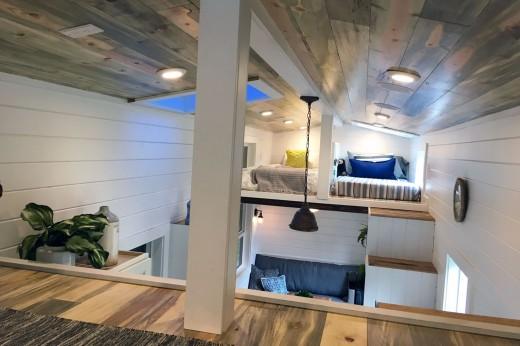 ロフトの天窓付きの低い勾配天井の下のベッドルームを、逆側のもう1つのロフトからのぞむ