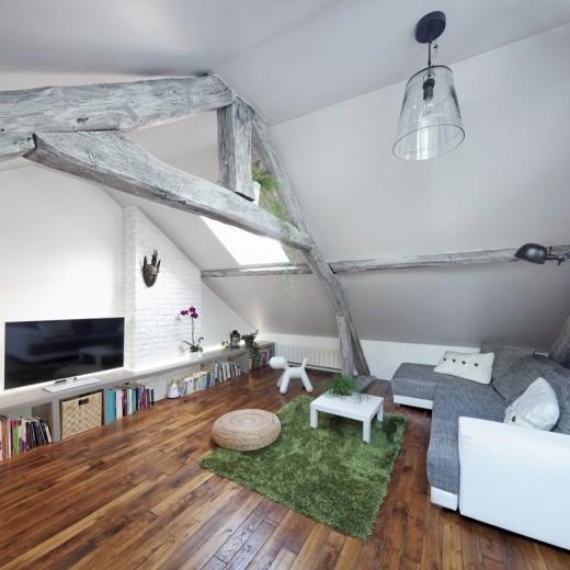 大きな天窓の入った勾配天井の下の包まれ感と開放感の共存するロフトのリビング