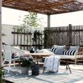 竹のソファと丸テーブルのあるパーゴラの下のウッドデッキの屋外リビング
