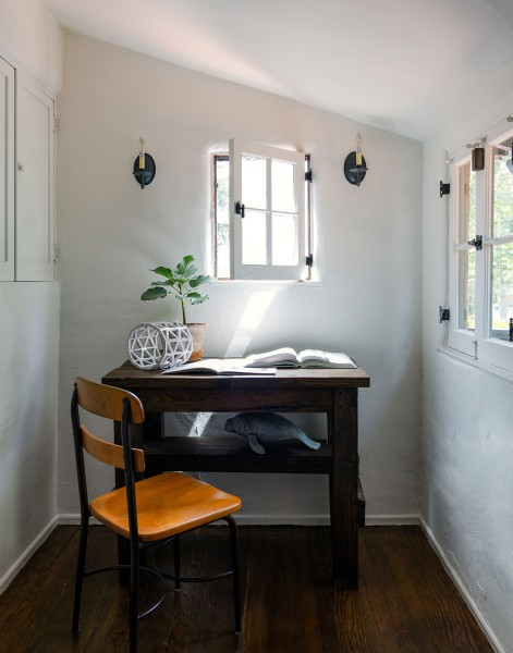 可愛らしい飾り格子小窓のある漆喰壁のコンパクトな書斎