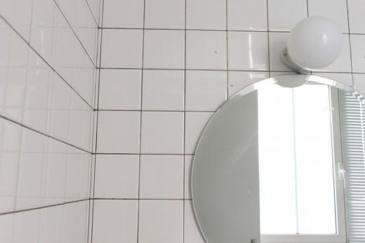 白いタイル貼りの明るく開放的な白基調のバスルームの鏡 タイルアップ