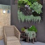 ラタンの一人掛け屋外用ソファとオットマンの置かれた庭のコーナースペース