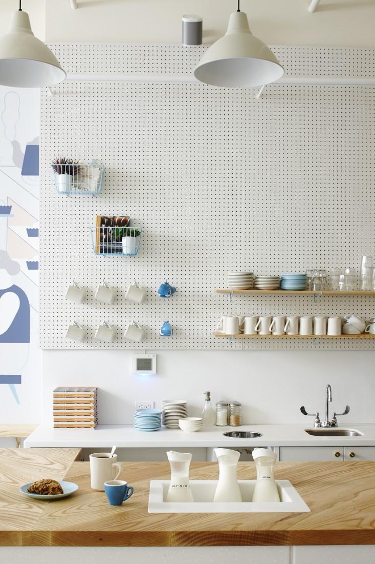 壁一面にオフホワイトの有孔ボードの収納スペースのあるキッチン