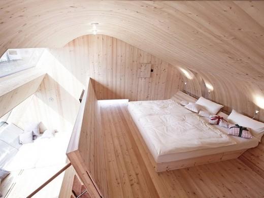 天井がドーム状にカーブした板張りのベッドルームとその下のデイベッドエリア
