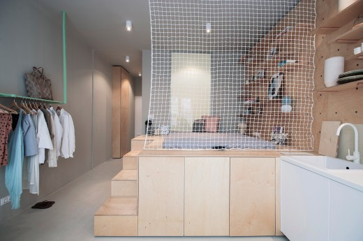 壁の合板に孔を開けて有孔ボードの壁面収納にしてあるダイニング・キッチンの脇のスキップフロアの小上がり的なベッドスペース