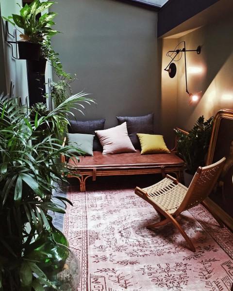 アースカラーと観葉植物がマッチした包まれ感のあるコンパクトなリビングスペース