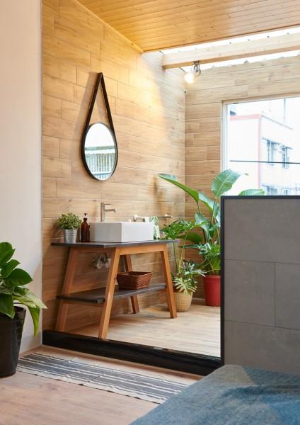 まるで屋外のように明るくて開放的な天窓と緑のある板張りのバスルームの洗面コーナをベッドルーム側から