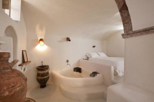 地中海風の白い漆喰で作られたギリシャ サントリーニ島のヴィラのベッドルームとバスルーム