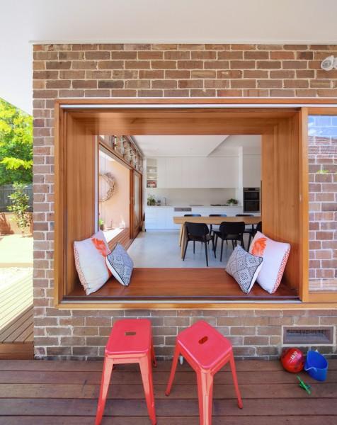 ダイニング・キッチンと庭の脇のウッドデッキのテラスをつなぐ、ベンチ付きの大きな開口窓