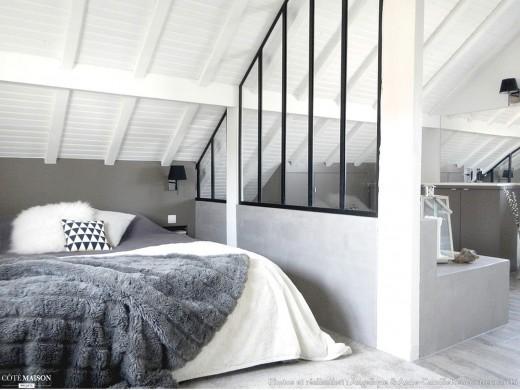 ガラスの間仕切り壁のある、勾配天井の下のロフトのベッドルーム