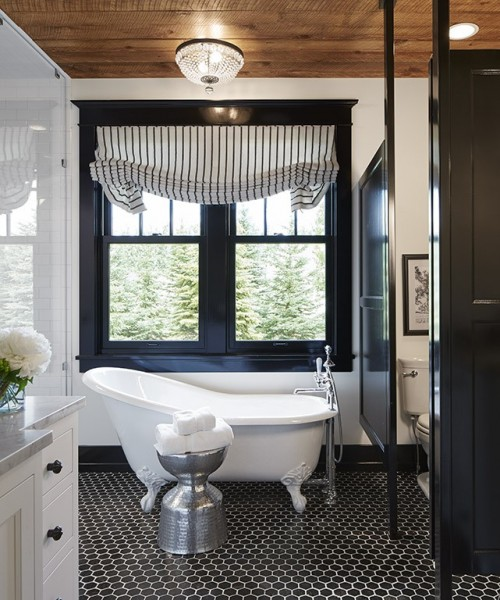 バスタブの脇の壁に2つの上げ下げ窓のあるシックな雰囲気のバスルーム