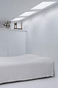 純白のベッドルームに天窓から差し込む光