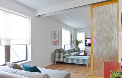 木製フレームとアクリル樹脂の半透明パネルのスライドドアで仕切られるリビングの一画 小部屋側から ドアを開けたところ