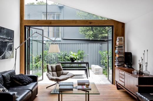 リビングと全開口のガラスドアで一体につながるコンパクトな中庭の屋外リビング