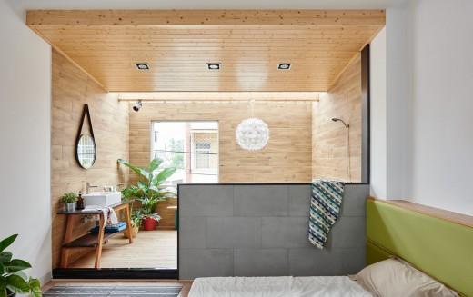 まるで屋外のように明るくて開放的な天窓と緑のある板張りのバスルームを隣接するベッドルームから
