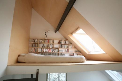 最上階の勾配天井の下に作られた、天窓と本棚付きのロフトベッドエリア