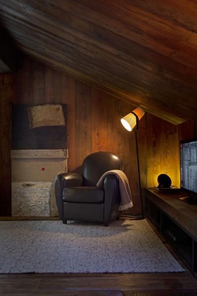 低い勾配天井の下のコーナーに一人掛けのソファを置いた寛ぎのスペース1