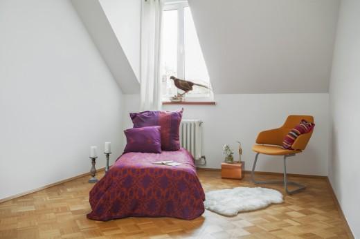 勾配天井と天窓の下に置かれた一人掛けソファのくつろぎスペース