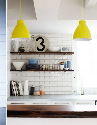 大胆でビビッドなレモンイエローのランプシェードが垂れ下がるダイニング・キッチン