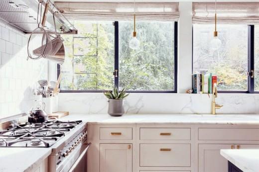 壁面全面の窓にシェードとハンギングランプが垂れ下がるキッチン