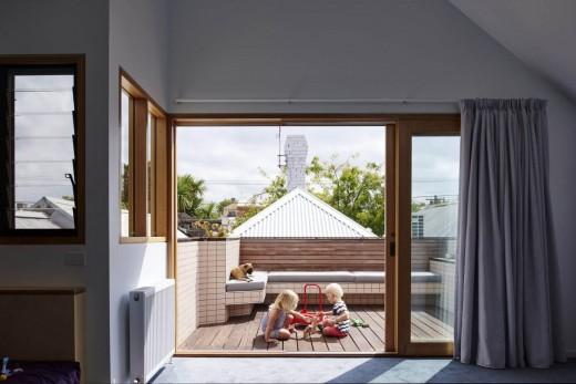 大きなガラスのスライドドアで屋内とつながる、デイベッド的な造作ベンチのあるウッドデッキのバルコニーの屋外リビング
