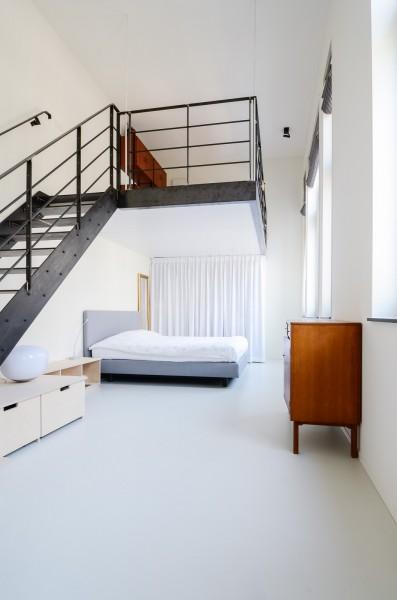 頭上にメゾネット的な中二階のロフトスペースのあるベッドルーム