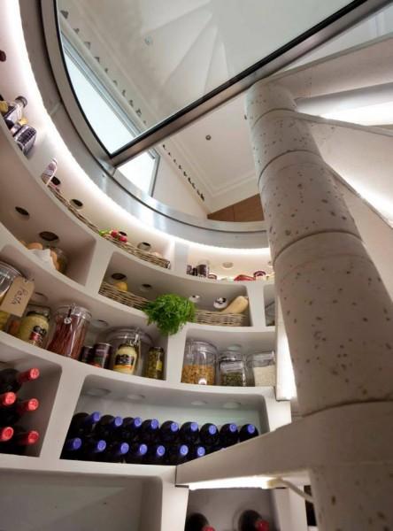 ダイニングの床に埋め込まれた、ガラス扉の螺旋階段状のワインセラー兼食料貯蔵庫の中から上を望む