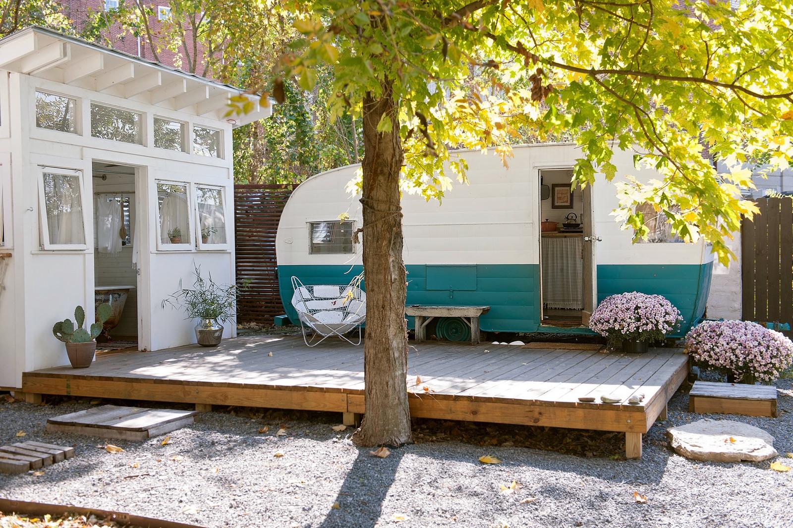 庭のウッドデッキと離れの脇に置かれたキャンピングトレーラーのベッドルーム