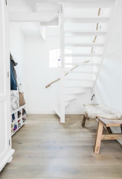 枝で作った手すりとニッチ状の出窓のある白いペンキ塗りの可愛らしい階段
