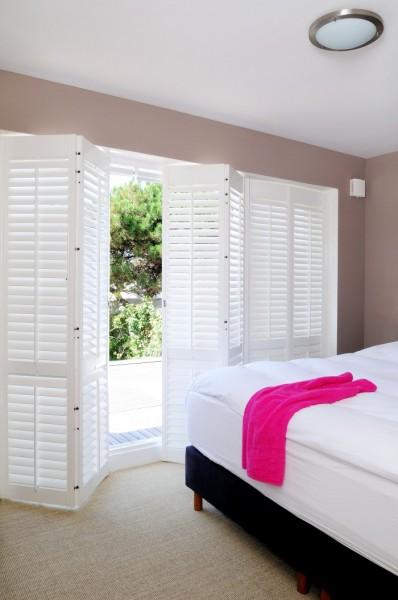 白い木製の折れ戸鎧戸で庭とつながるベッドルーム2