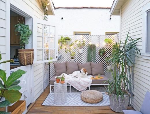 屋外家具のソファの置かれたリビング・ダイニングに隣接するコンパクトな庭 ウッドデッキのテラス