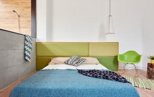 まるで屋外のように明るくて開放的な天窓と緑のある板張りのバスルームに隣接するベッドルーム