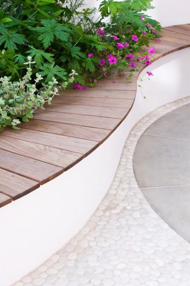 白い小石のテラスに造作された曲線のウッドベンチ
