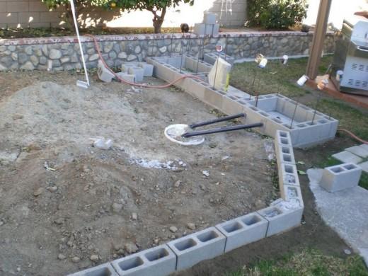 DIYで作った、レンガのカウンターやBBQグリル、シンクのある立派なアウトドアキッチン DIY06 排水管の周りをセメントで埋める