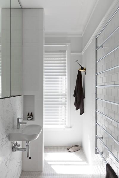 ヘッドボードの向こう側の細長いバスルーム 裏側の洗面スペース
