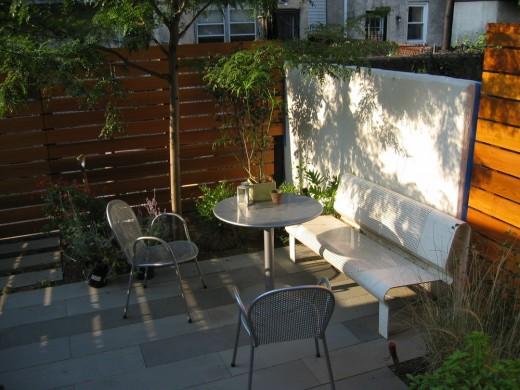 石畳のコンパクトな庭に屋外家具のテーブルとベンチ、チェアを置いて屋外ダイニングに