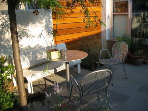 コンパクトな庭の屋外ダイニング サイカチの木の下に置かれた屋外家具のテーブルとベンチ