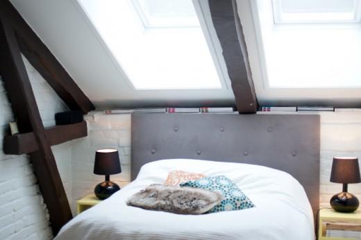 勾配天井の天窓の下のベッドルーム