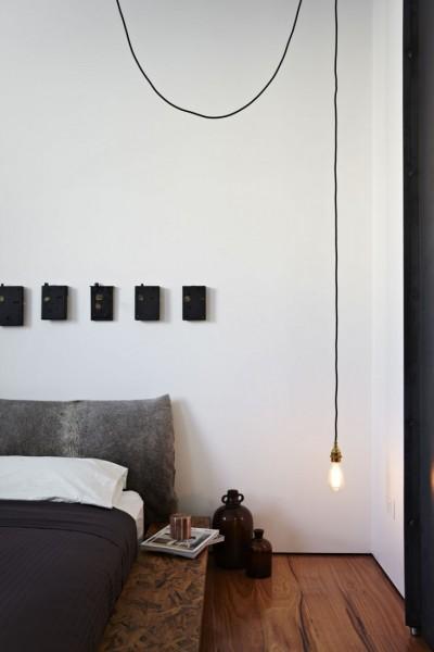 ベッドサイドに天井からぶら下がる裸電球のペンダントライト